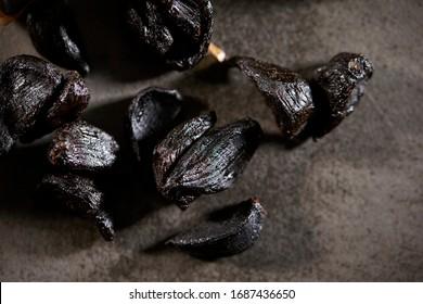 Fermented black garlic on stone background