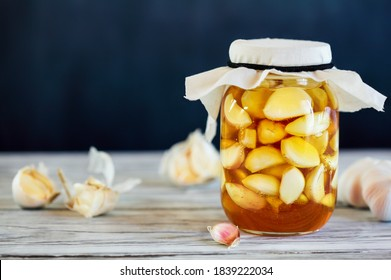 Fermented garlic cloves in a jar of honey, a rich source of probiotics, over a rustic wood background table. Selective focus with blurred background and foreground.