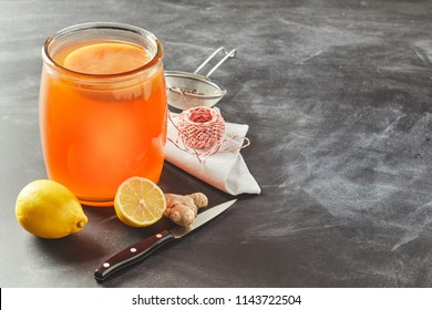 Fermented glass jar of black tea kombucha with fresh lemon and root ginger on a slate background with copy space