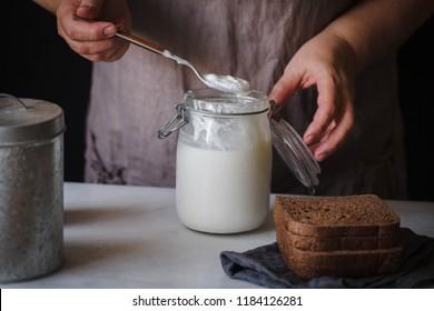 Fermented probiotic drink kefir Bottle of kefir drink hands rustic table