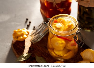 Fermented yellow squash vegetable in a glass jar. The concept of canned food. Garlic in the foreground
