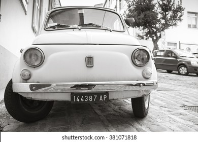 Fermo, Italy - February 11, 2016: Old white fiat 500 L city car on the street of Italian town, close-up front view, monochrome photo