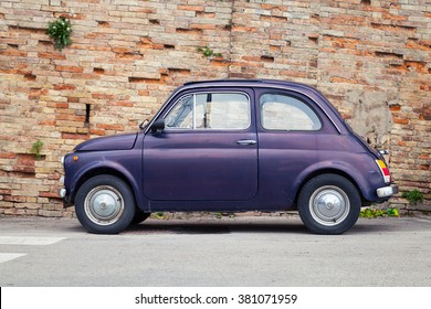 Fermo, Italy - February 11, 2016: Old Fiat Nuova 500 city car produced by the Italian manufacturer Fiat between 1957 and 1975 stands in a town, side view