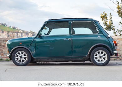 Fermo, Italy - February 8, 2016: Dark green Austin Mini Cooper Mk III side view. This modification of Mini is a small economy car made by the British Motor Corporation between 1969 and 1976