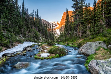 Fern creek flows out of Odessa Lake below Notchtop Mountain and the Ptarmigan Pass seen through the forest in Rocky Mountain National Park, Colorado.