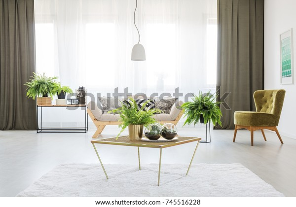 Varen op een tafel in monochromatische woonkamer met groene stoel, olijfgordijnen en grijze bank