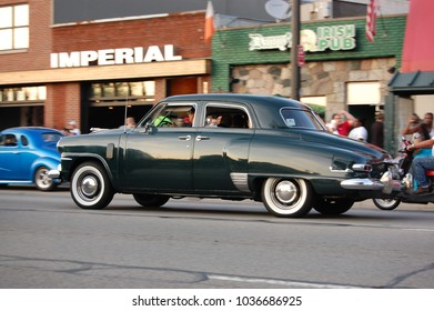 Ferndale, MI/USA-August 17 2013 Dark 1949 Studebaker Champion driving at the annual Woodward Avenue Dream Cruise, metro Detroit. Classic autos, white walls, chrome and crowds and fun at the car show!