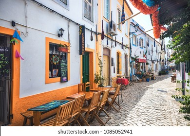 Ferragudo, Algarve Region, Portugal, August 15, 2016: Terraces of restaurants in a paved alley of Ferragudo village, Algarve region, Portugal