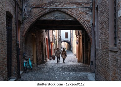 FERRARA, ITALY - 31. 12. 2018: Couple marching through the street Via delle Volte