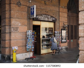 Ferrara, Italy - August 15, 2018. Old lady looks at the window of a tobacconist in the historic center.