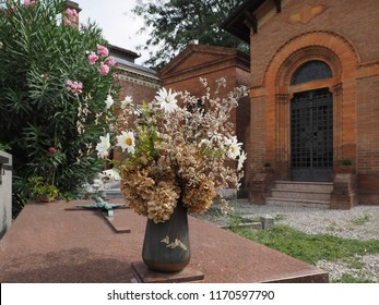 Ferrara, Italy - August 25, 2018. Certosa monumental cemetery. Flowers next to the gravestones.