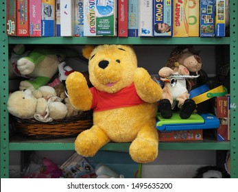 Ferrara, Italy - August 27, 2019. Flea market. Children's game shelves, board games, plush toys and a large Winnie the Pooh plush.