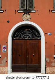 Ferrara, Italy - August 27, 2019. Large entrance door, above the entrance there is an ancient terracotta tile depicting the Madonna and Child Jesus.