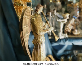 Ferrara, Italy - December 25, 2019. Showcase of a shop displaying Christmas items. In the foreground is the figurine of an angel playing the trumpet.