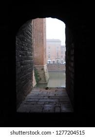 Ferrara, Italy - December 27, 2018. Este Castle, detail. Looking through a loophole.