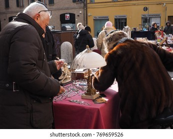 Ferrara, Italy - December 3, 2017.  Monthly flea market in the historic centre. A stall sells costume jewelry, two people are buying.