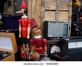 Ferrara, Italy - January 6, 2018. Flea market in the historic center. Two Pinocchio next to old radios.