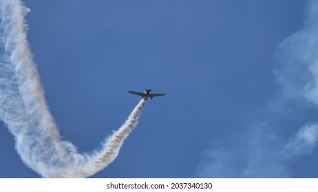 Ferrara Italy JUNE, 27, 2021 Small airplane rises vertically in the blue sky with white smoke trail. Corby CJ-1 Starlet single seat, amateur built airplane of the 1960s