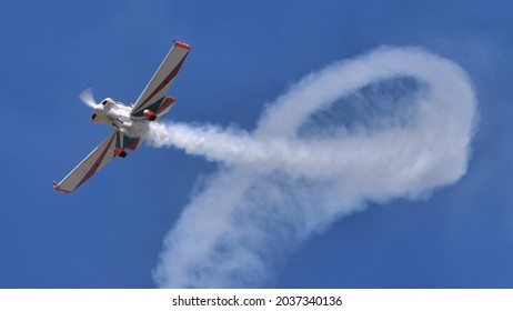 Ferrara Italy JUNE, 27, 2021 Small propeller aerobatic plane draws a loop with its white smoke trail in the blue sky. Corby CJ-1 Starlet single seat, amateur built airplane of the 1960s