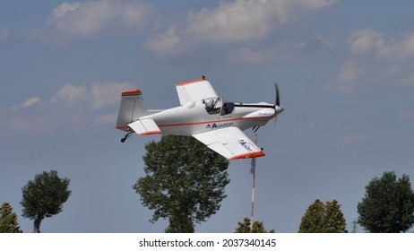 Ferrara Italy JUNE, 27, 2021 Small propeller aerobatic plane flying at low altitude with trees in the background. Corby CJ-1 Starlet single seat, amateur built airplane of the 1960s