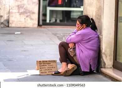 Ferrara, Italy - June, 9, 2018: the beggar begging in the old town of Ferrara, Italy