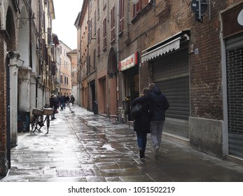 Ferrara, Italy - March 17, 2018. Via San Romano, medieval street in the historic center. Two lovers walk after the rain.