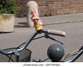 Ferrara, Italy - May 16, 2018. Bicycle handlebars and a bell shaped like a cute dragon.