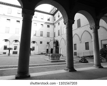 Ferrara, Italy - May 27, 2018. Este Castle. The inner courtyard seen from under the arches, in the middle the well of the castle. Black and white photo.