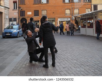 Ferrara, Italy - November 26, 2018. Piazza Trento e Trieste, the main square. Christmas market and tourists taking photographs with a cell phone.