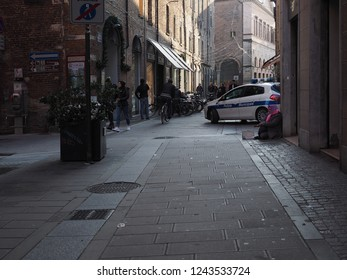 Ferrara, Italy - November 26, 2018. Historical centre, municipal police car, a woman asking for alms.