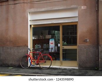 Ferrara, Italy - November 26, 2018.  The window of a laundry. In front of the shop there is a red bicycle.