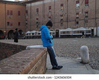 Ferrara, Italy - November 26, 2018. Historic centre, near the castle. Men watching their cell phone.