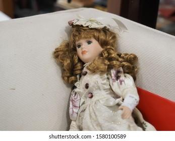 Ferrara, Italy - November 28, 2019. Flea market. Face of vintage doll with a sad expression.