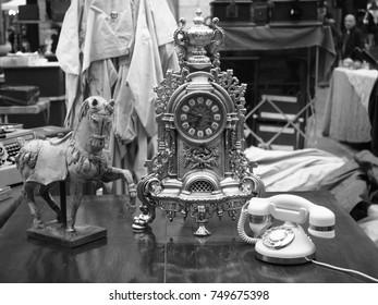 Ferrara, Italy - November 4, 2017. Flea market in the main square. Small horse statue, antique decorated clock, vintage phone. Black and white photo.