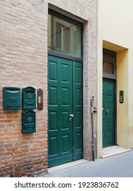 Ferrara, Italy. Old building, two green doors and three mailboxes.