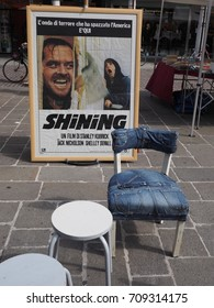 Ferrara, Italy - September 2, 2017. Garage sale: italian movie poster and jeans covered chair.