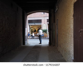 Ferrara, Italy - September 8, 2018.  Covered alley that leads into the Duchesse Park, next to the castle. In front there is a fruit and vegetable shop.