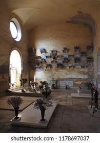 Ferrara, Italy - September 9, 2018. Certosa monumental cemetery. Interior room, tombs and flowers.
