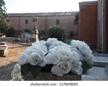 Ferrara, Italy - September 9, 2018. Certosa monumental cemetery. Cloth flowers over a grave.