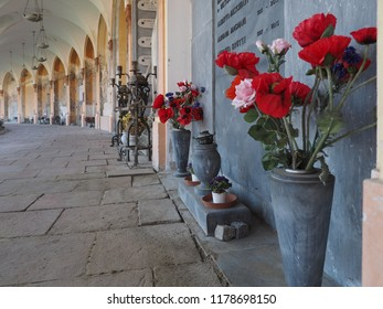 Ferrara, Italy - September 9, 2018. Certosa monumental cemetery. Porch with tombstones and flowers.