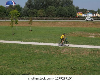 Ferrara, Italy. September 9, 2018. A cyclist in the path of the medieval walls, in the background the Balloons Festival and a hot air balloon.