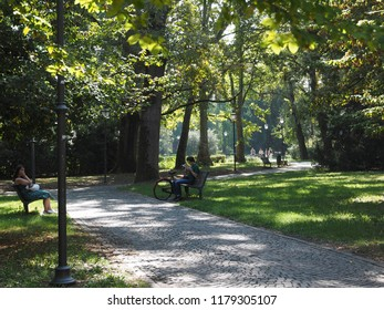 Ferrara, Italy. September 9, 2018. Parco Massari, people relaxing on the benches.