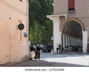 Ferrara, Italy. September 9, 2018. The arcades of Piazza Ariostea. A woman on a bicycle, two tourists.