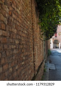 Ferrara, Italy. September 9, 2018. Ancient wall and in the background the arcades of Piazza Ariostea.