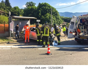 Ferrera di Varese, Varese, Italy - June 26, 2018: Damaged car on the provincial road with ambulance assistance to the victim in Ferrera di Varese, Italy