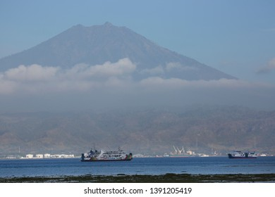 Ferries sailing up and down the sea channel between Bali and Java islands, view at vulcano Gunung Raung