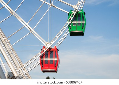 Ferris wheel's green and red colored cabs on a Blue Sky background in Almaty