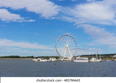 Ferris of National Harbor in Oxon Hill, Maryland, USA. Boats and yachts at National Harbor pier on a bright sunny day.