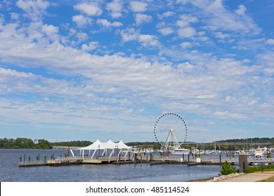Ferris of National Harbor and piers in Maryland, USA. National Harbor waterfront on a bright sunny day.