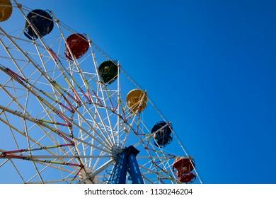 Ferris wheel against the blue sky. Amusement park.